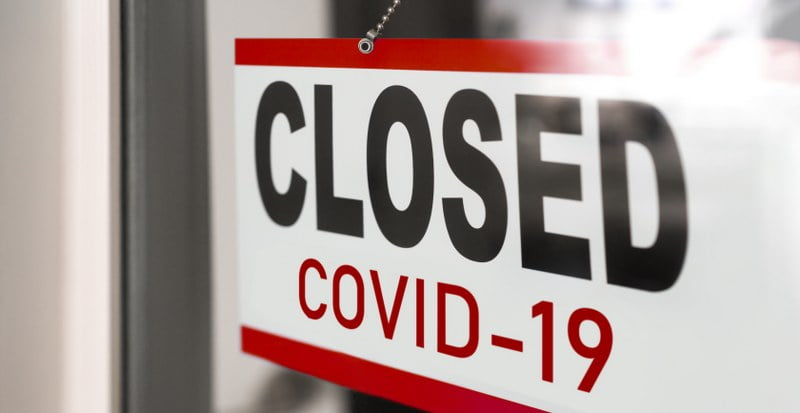a closed sign due to covid-19 on storefront