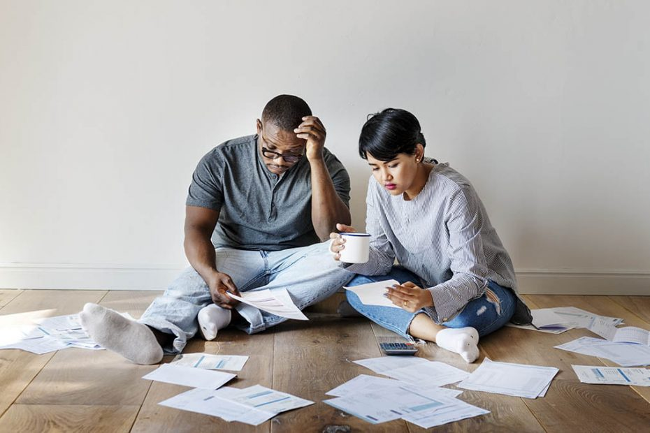 Couple sits on the floor with bills scattered around