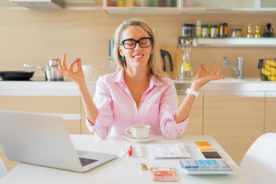 Woman with a pink shirts sits behind a somewhat messy desk arranges her hands in a meditation pose