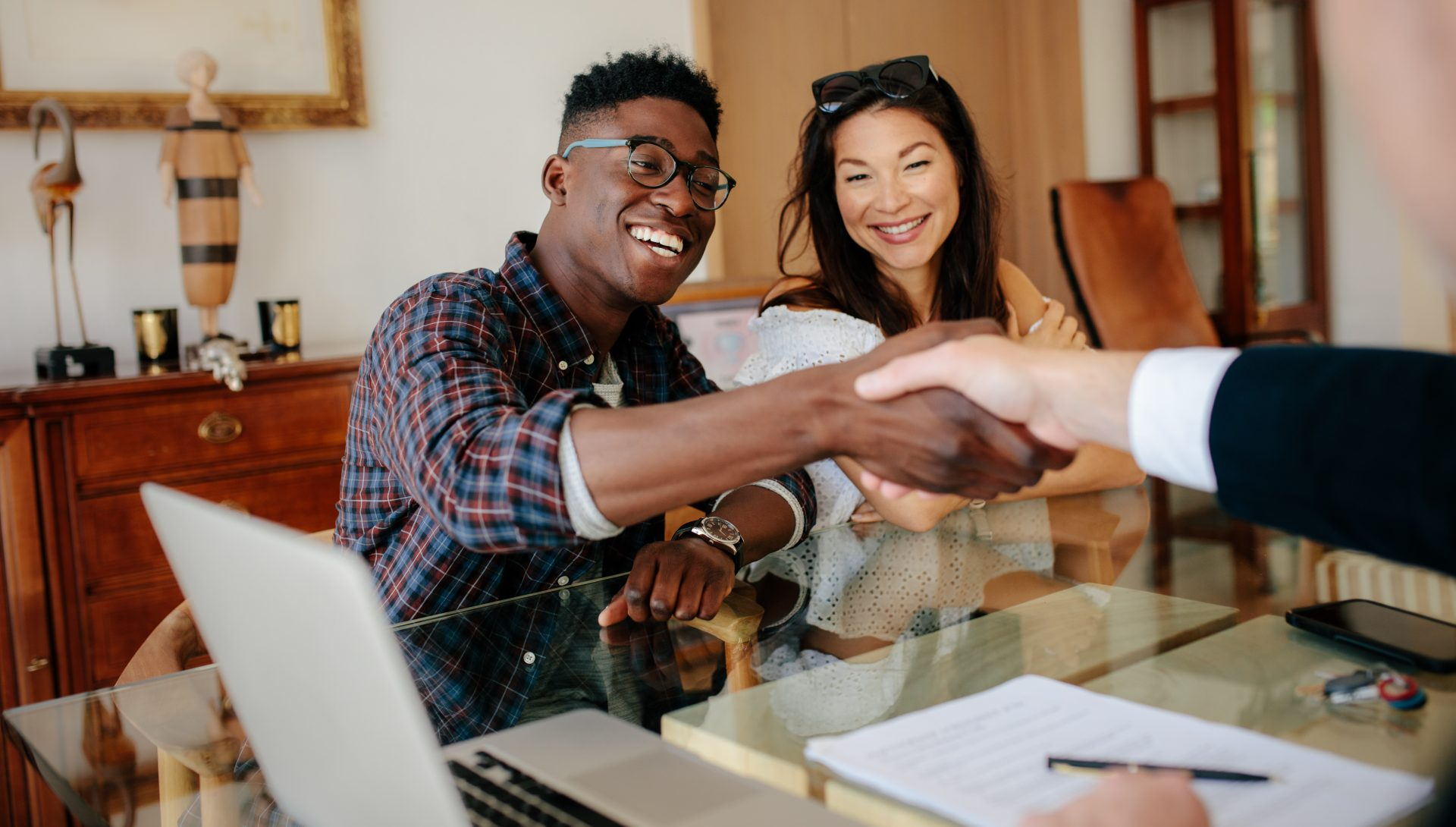 Couple shaking hands with a salesman across a desk
