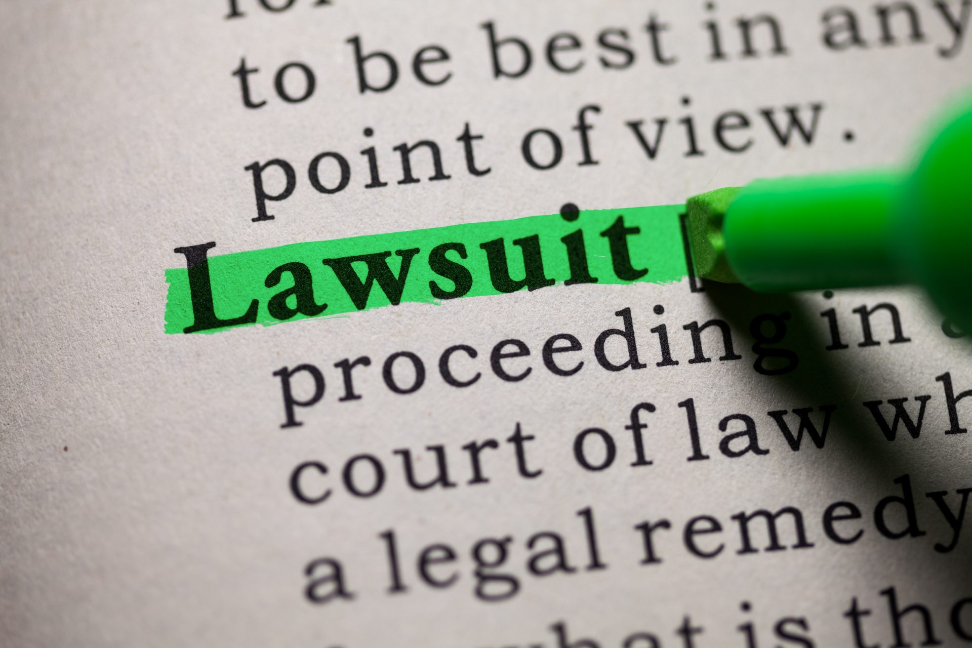 """Photo of a dictionary definition of """"lawsuit"""" being highlighted in green"""