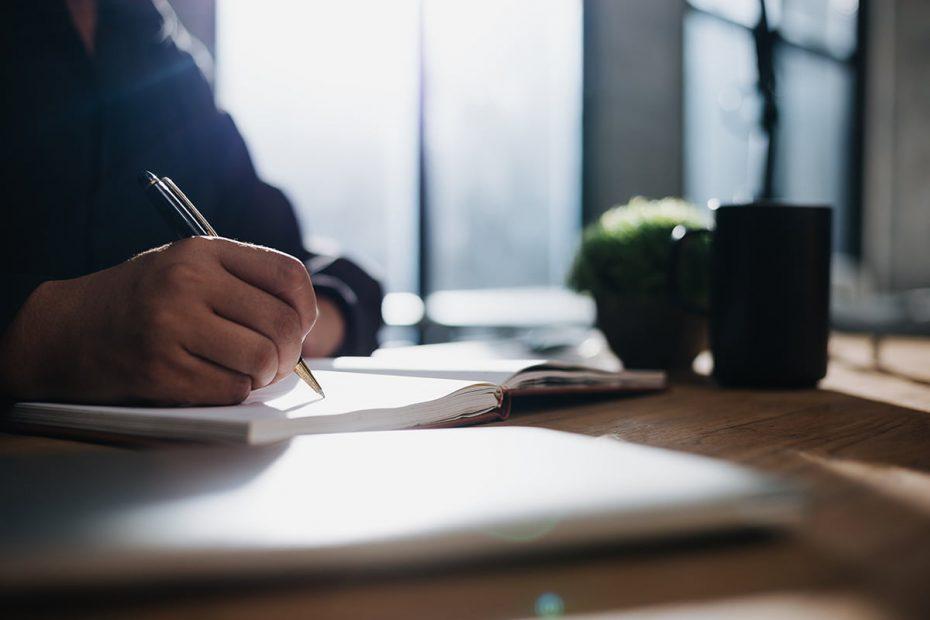 A man sits at a desk making a checklist