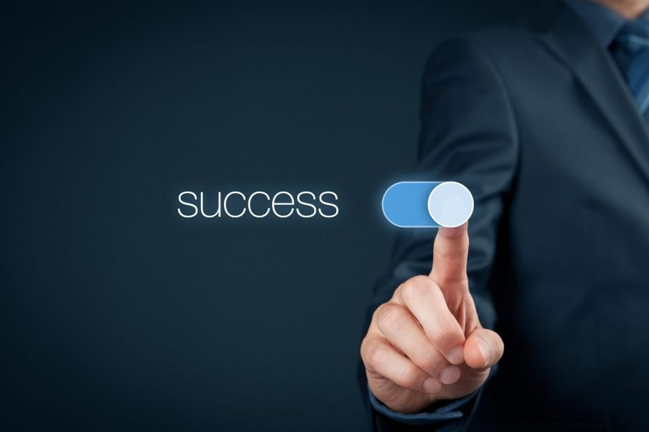 "Man in a business suit moves a digital slider next to the word ""success"""